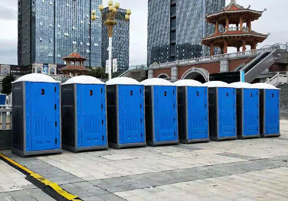 Eight EPS Portable toilets in front the high buildings outdoors