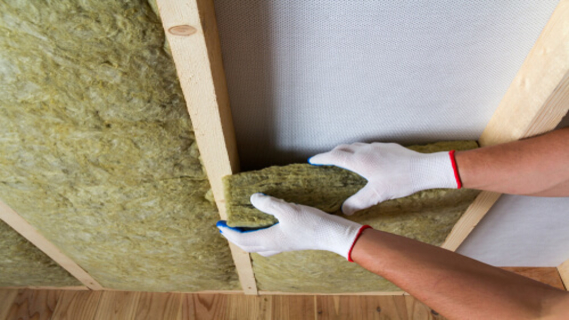 Close-up of worker hands in white gloves insulating rock wool insulation staff in wooden frame for future walls for cold barrier