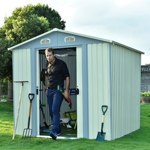 A man walking out of the door from a garden shed